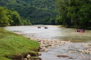 A group of three rafts paddle down a Class 1 river on a rafting trip on the Amazon river.