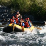 A group in a raft tackling white water rapids on a Class 3 River.