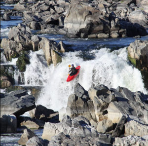 A kayaker descending a waterfall on a Class 6 river.
