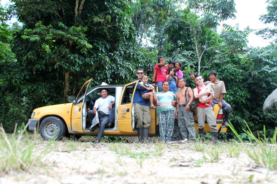 All of the Raft Amazonia family smiling for the camera in front of Luis's taxi.