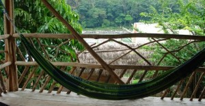 A hammock with a view of the Amazon jungle and river behind.