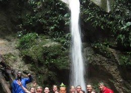 A group of travellers stand below a waterfall in the Amazon Jungle.