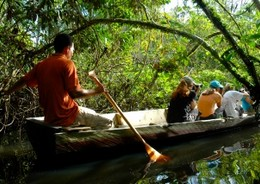 A group of travellers experiencing a tour of the Amazon river in a traditional carved canoe.