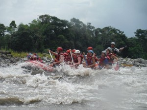 A group on a white water rafting tour on the Amazon river.