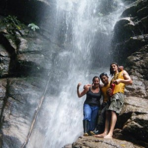 Three people standing by a waterfall in the Amazon jungle.